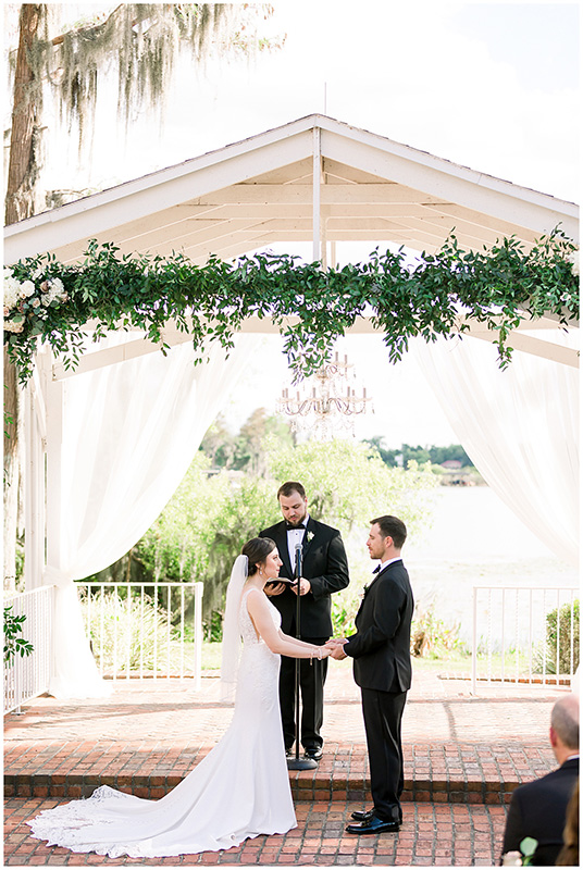 The bride and groom are standing in front of the officiant, looking into each other's eyes and holding hands.