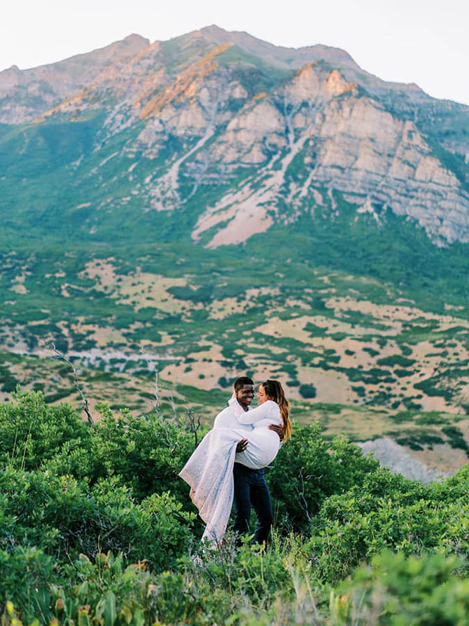 A groom is carrying his bride in the middle of a field near the Provo Canyon in Utah.