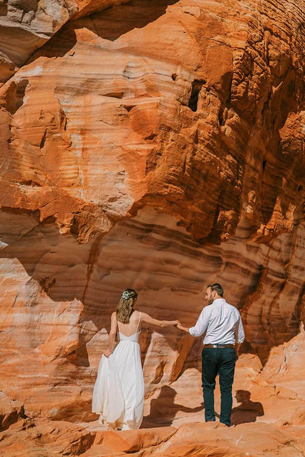 A wedding couple is holding hands and facing a orange mountain at the Valley of Fire State Park.