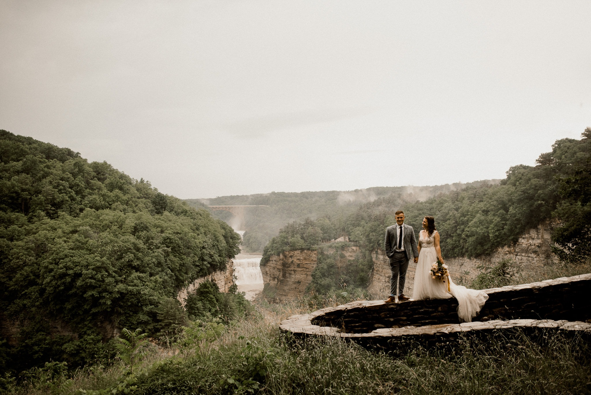 A wedding couple is standing on a wall and holding hand at the Letchworth State Park