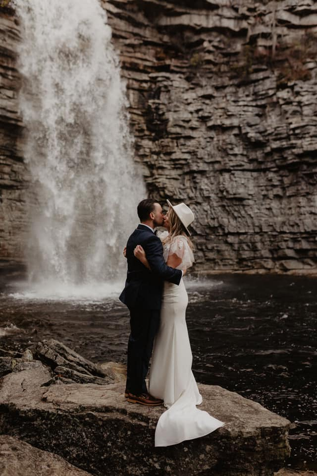A wedding couple is kissing each other and standing on a rock with a waterfall behind them at the Awosting Falls.