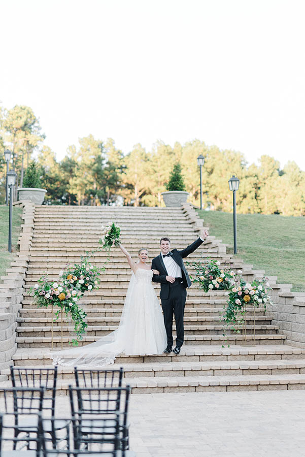 A wedding couple is standing in front of an impressive staircase near Swan Lake Overlook.