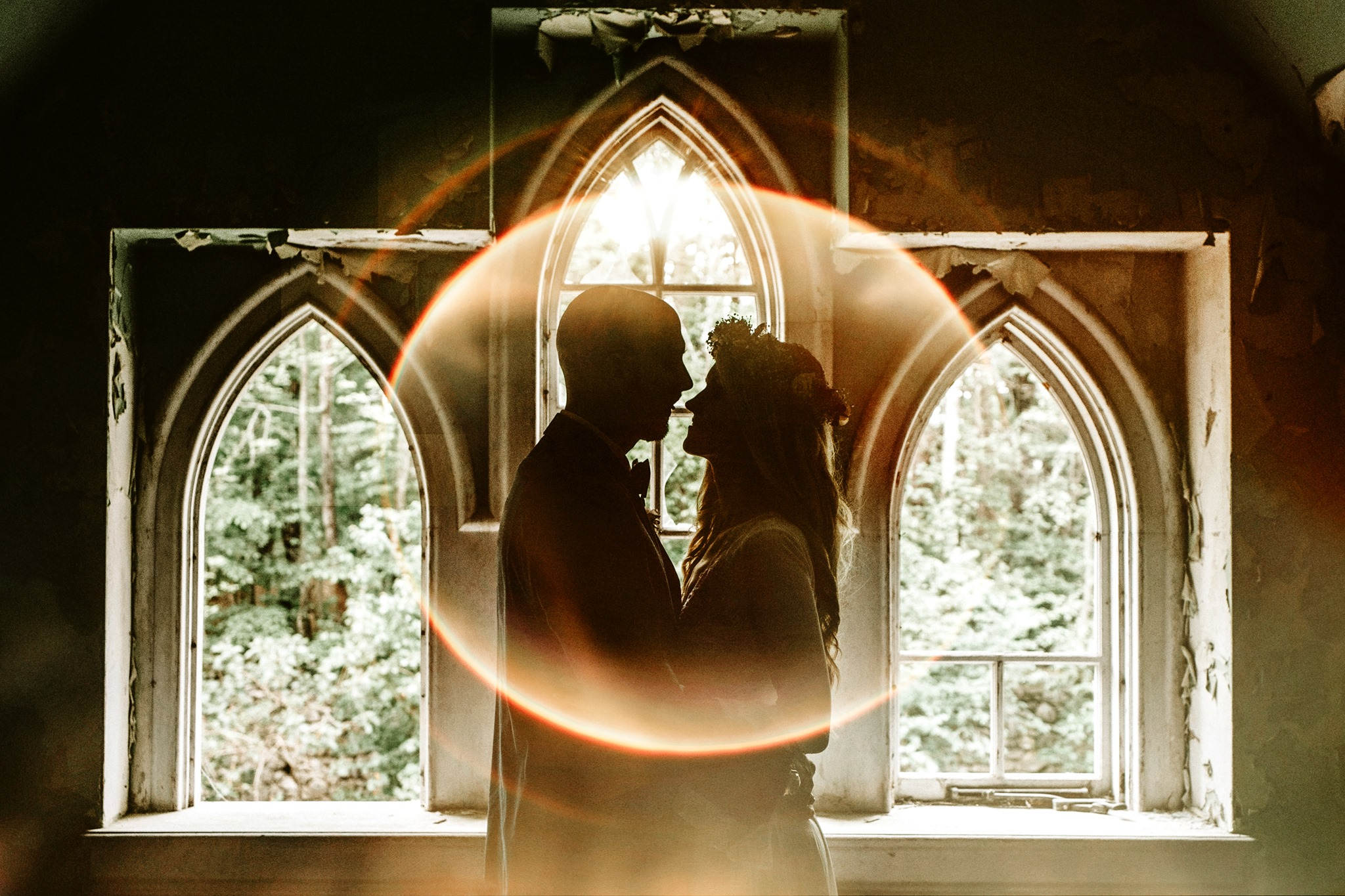 A wedding couple is holding each other and in the background are windows of the Dundas castle.