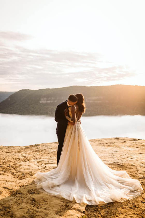 A groom is kissing his wife on her neck whilst and the couple is standing on a sandy plateau at the Signal Mountain in Tennessee.