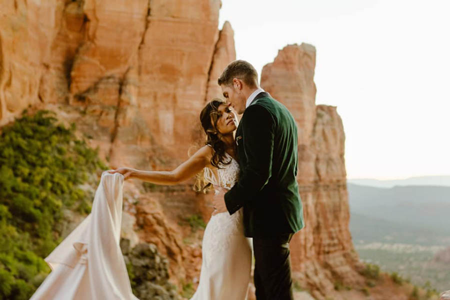 A wedding couple is holding each other and the bride is holding her dress and they are standing near mountains in Sedona.