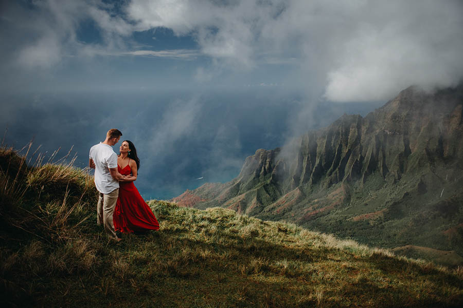 A couple is holding each other and looking at each other whilst standing on a field of grass on a mountain in Kauai.