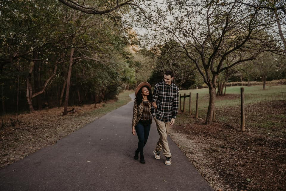 An engaged couple is walking on a road at the McDaniel farm park in Georgia.