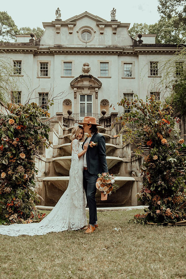 A wedding couple is standing in front of a fountain right in front of the swan house at the Atlanta history center.