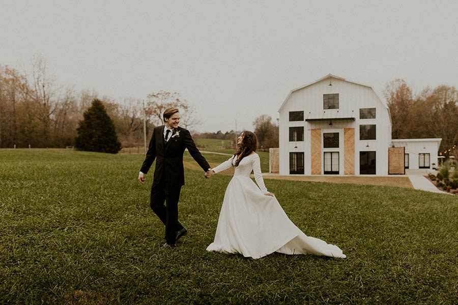 A wedding couple is holding each other and walking on a field win front of the Barn South.