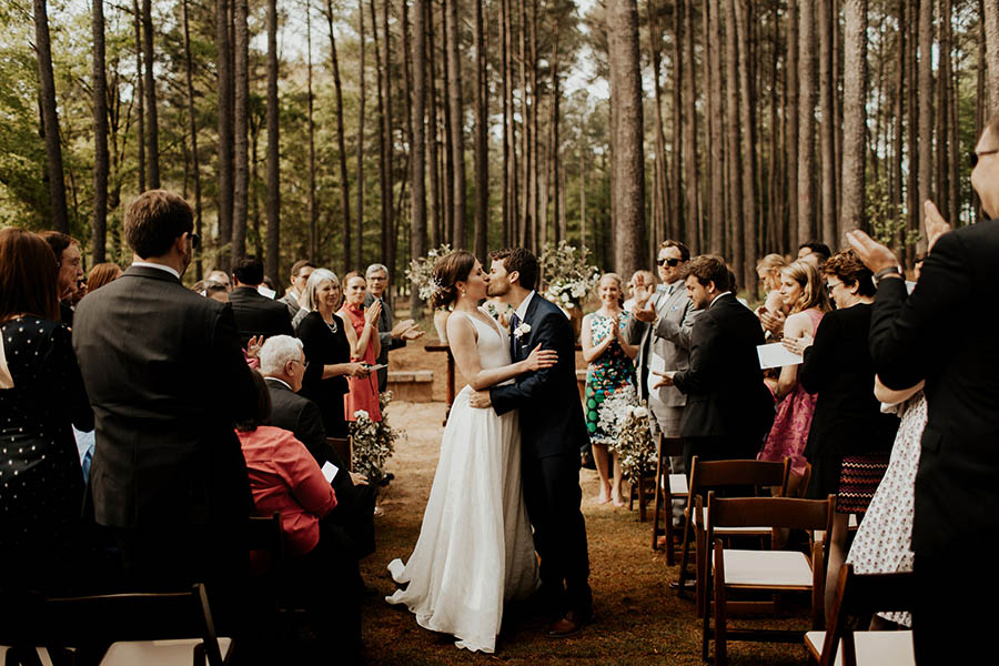 A wedding couple is standing in a forest in-between their guests and kissing each other at the inn at serenbe.