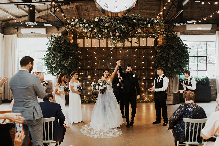 A wedding couple just got married and is standing in the middle of the aisle, holding each other and cheering, to the right and left of the aisle are their guests sitting at the soho south cafe.
