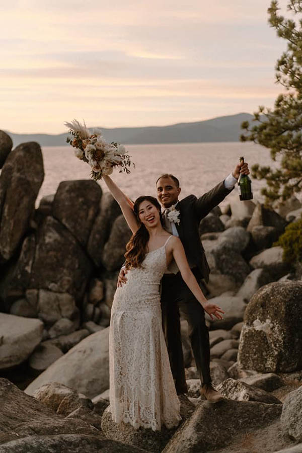 A wedding couple is standing on rocks in front of Lake Tahoe in Nevada and cheering whilst holding a bouquet and a bottle of wine.