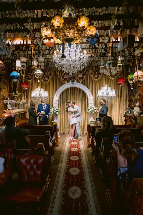 A wedding couple is kissing each other and standing in a colorful room at the end of an isle with a few wedding guests sitting next to the isle in New Orleans.