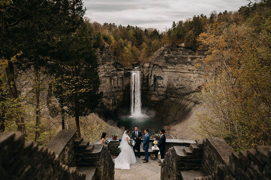 A wedding couple is standing in front of the Taughnnock Falls and getting married.