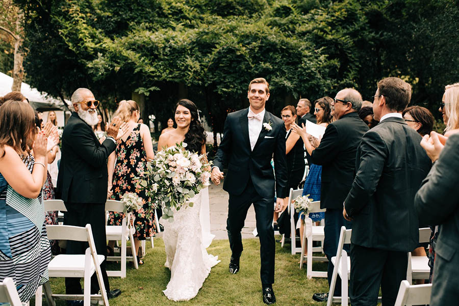 A wedding couple is walking down the aisle and their guests are standing to the left and right of the aisle and are cheering and clapping their hands at the gator woolford gardens.