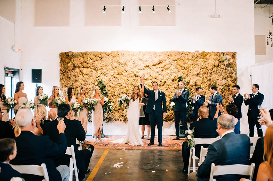 A wedding couple is holding hands and standing in the middle of the aisle, wedding guests are sitting to the right and left of the aisle in the Monday night brewery.