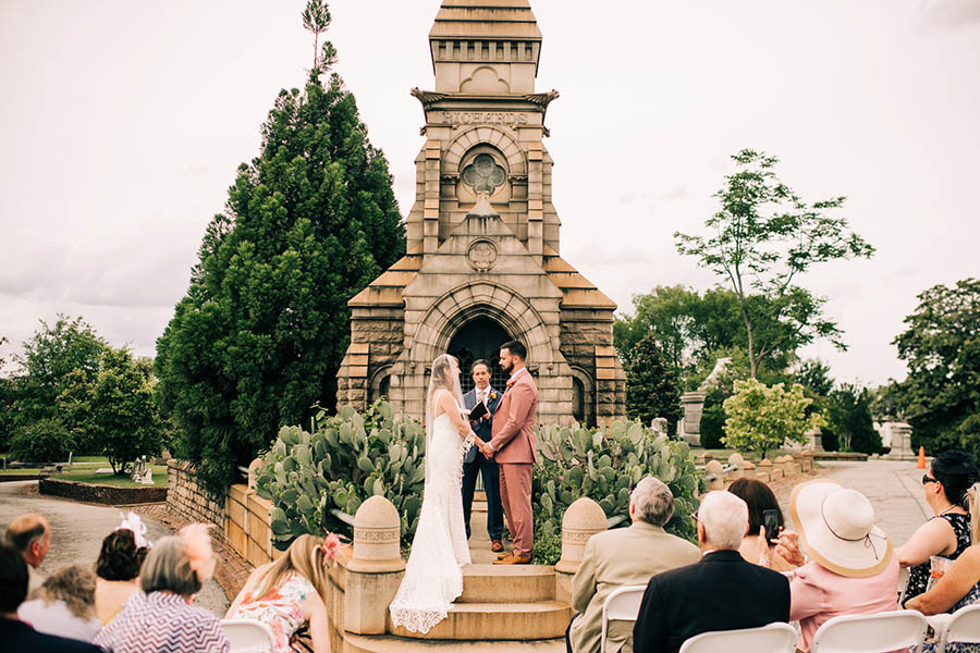A wedding couple is holding each others hands and standing in front of a chapel in the Oakland cemetary.