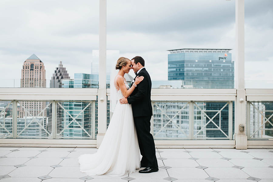A wedding couple is holding each other and touching each others foreheads and standing on top of a high building at the peach tree club.