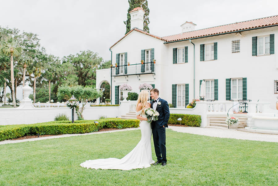 A wedding couple is smiling at each other and standing on the lawn in front of a house at the Jekyll island resort.
