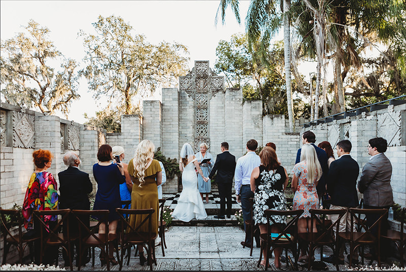 A wedding couple holds hand while the officiant speaks at their wedding ceremony taking place in a historic outdoor Museum