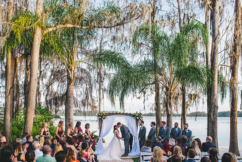 The groom and bride are kissing in front of their wedding guests after they said I do.