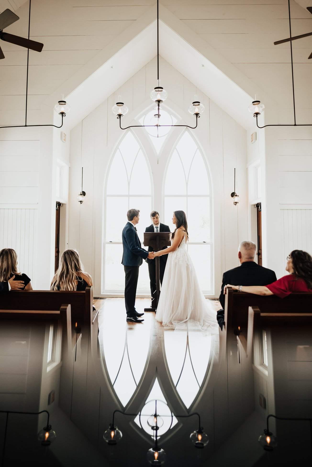 a wedding ceremony taking place in a chapel with a low number of guests