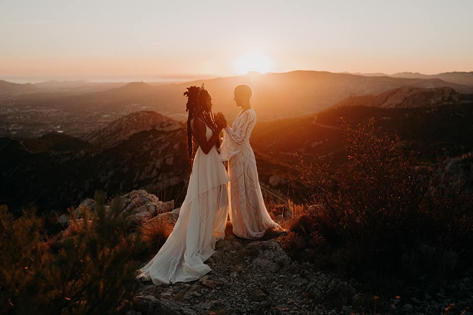 Two brides are holding hands and standing on a mountaintop with a sunset in the background.