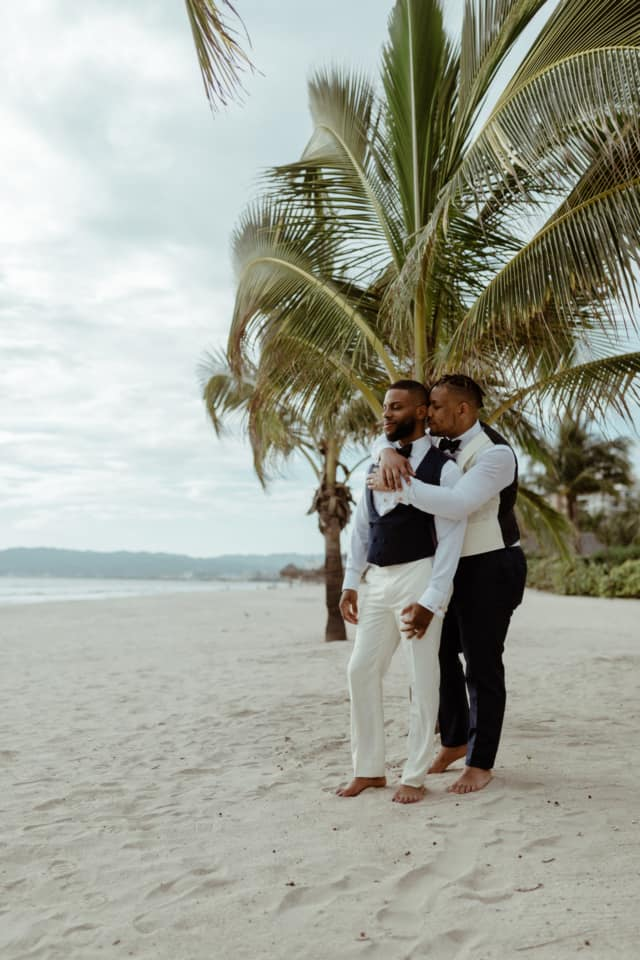 Two grooms are holding each other and standing on a beach at Puerto Vallarta.