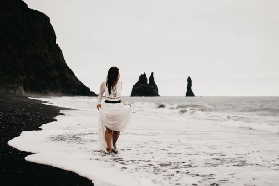 A bride is walking along the black sand beach in Iceland.