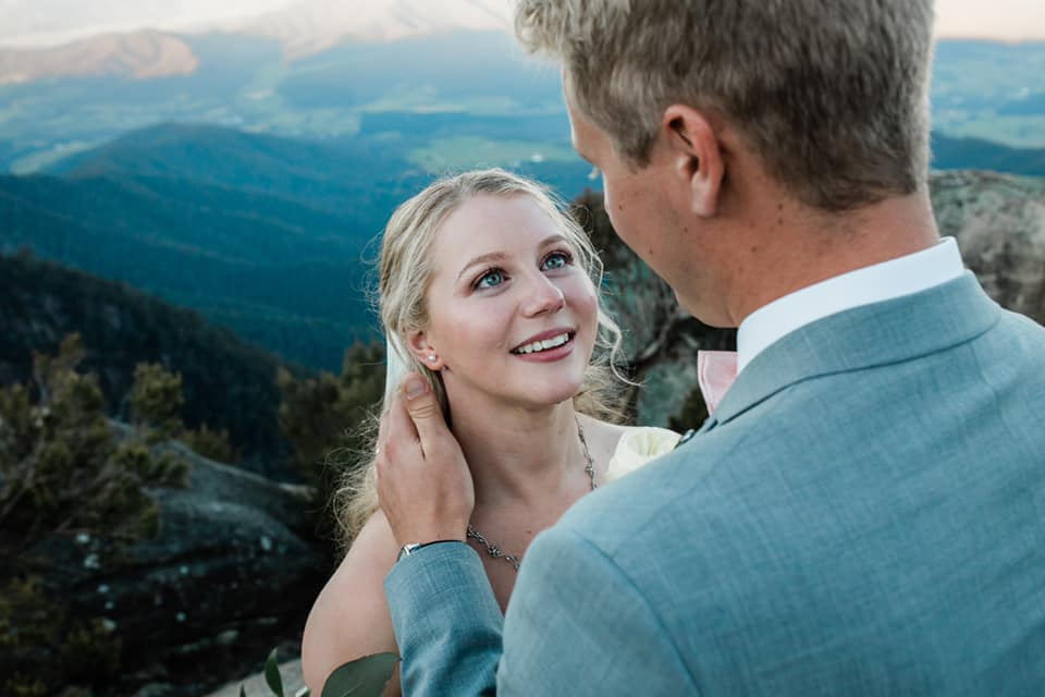 A wedding couple is standing on a mountain at looking at each other.