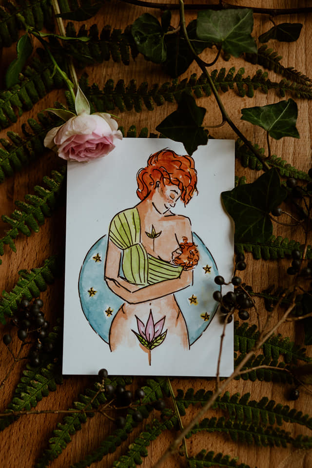 a painted image of a breastfeeding mother lays on a wooden surface surrounded by farn and a rose