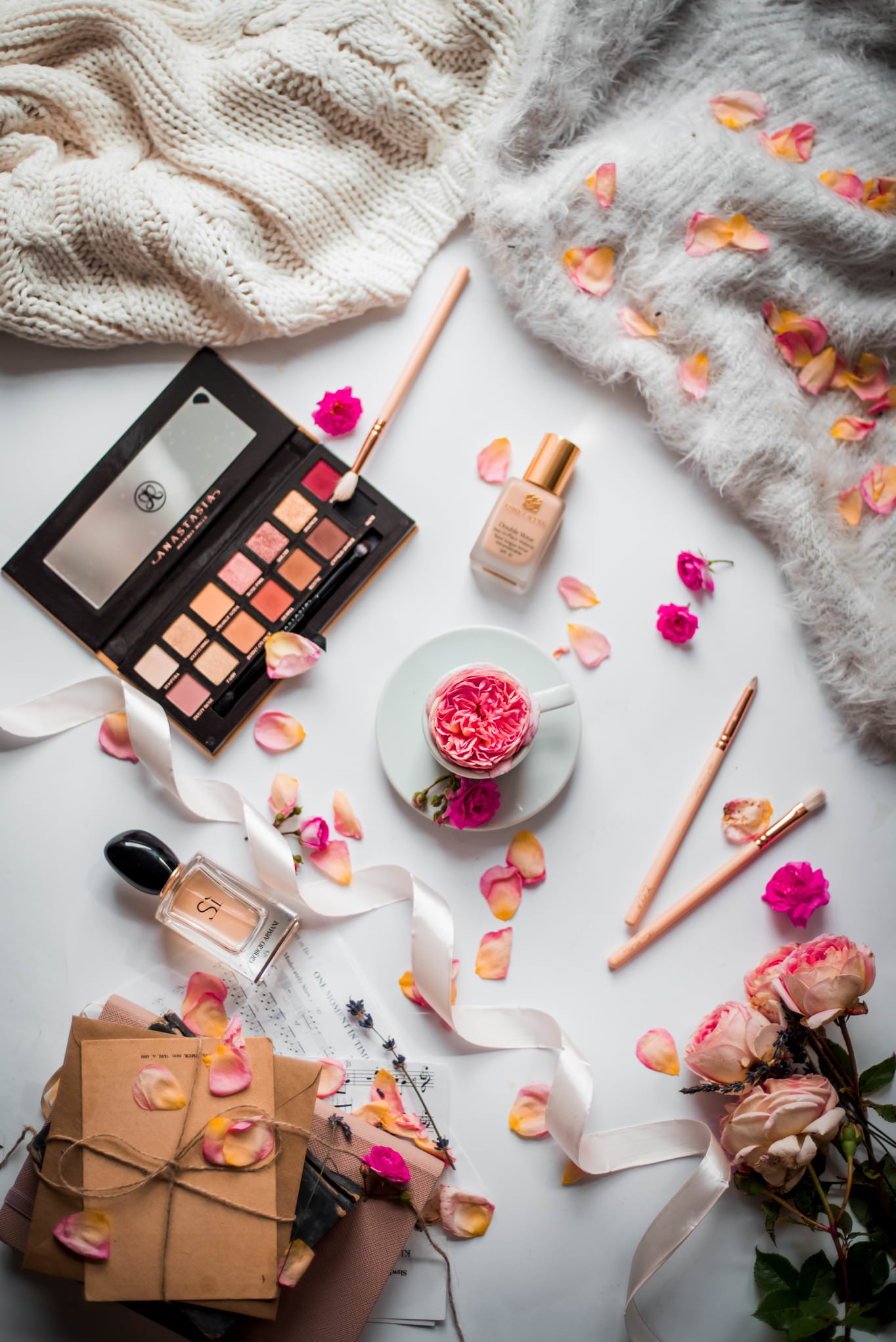 makeup objects decorated with rose flowers on a white surface