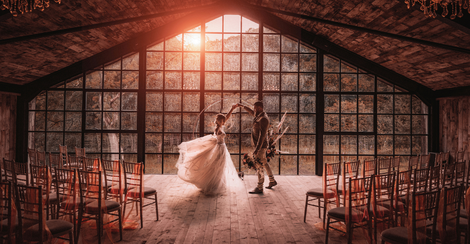 A wedding couple is dancing in front of a glazed wall.