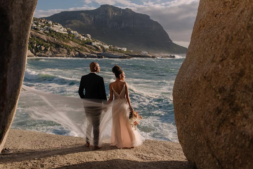 A wedding couple is standing on rocks near the ocean and is holding hands near Capetown.