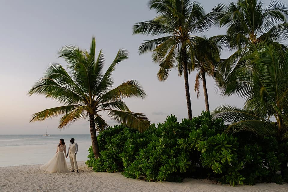 A wedding couple is standing on the beach in Zanzibar.