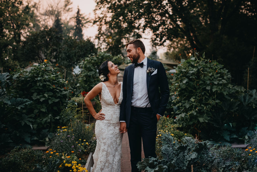 A wedding couple is holding hands and standing in a garden.