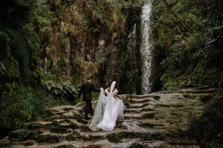 A wedding couple is walking up stairs made of rocks towards a waterfall.