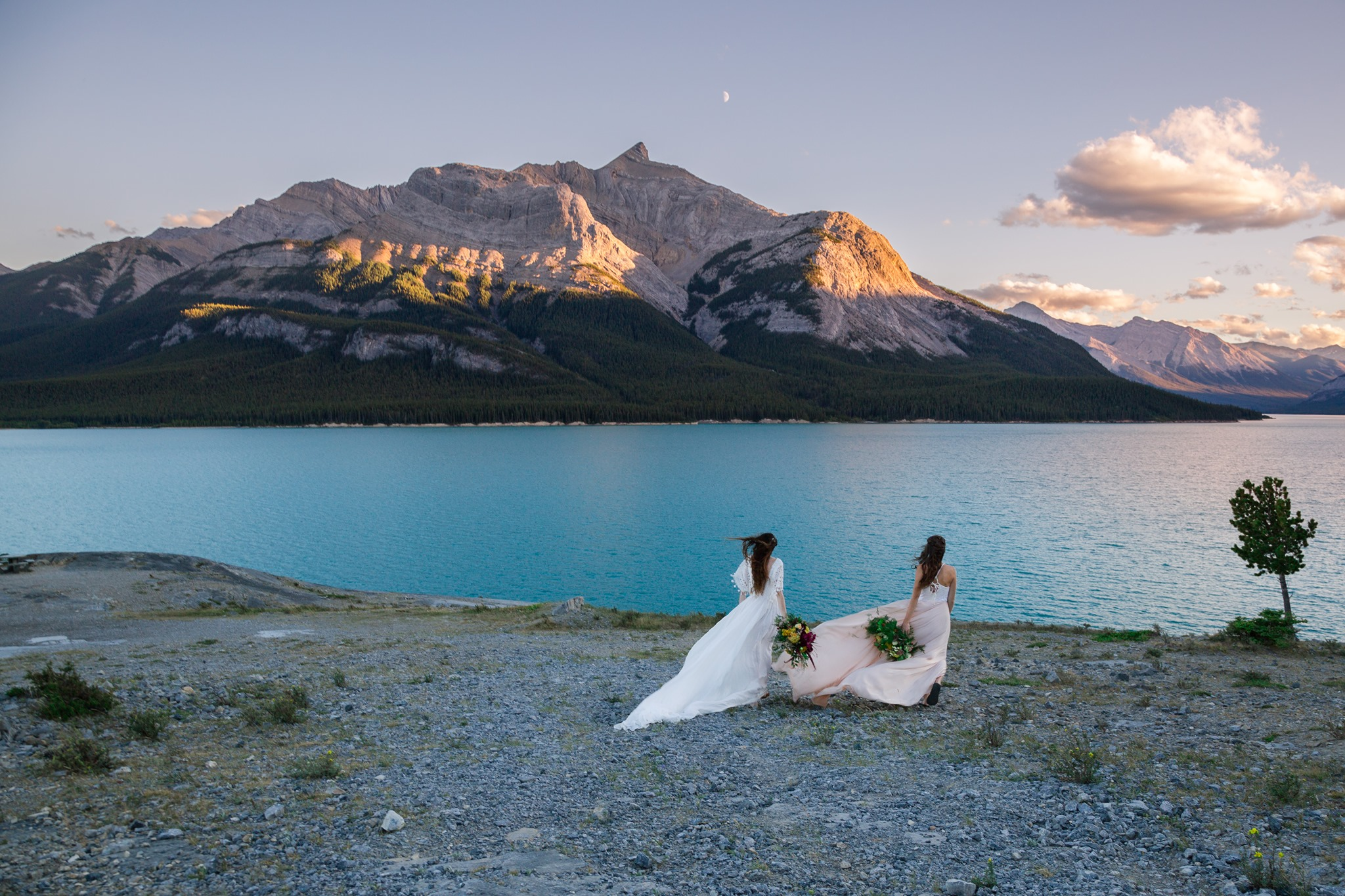 Two brides are standing in front of Abraham Lake and looking towards the lake.