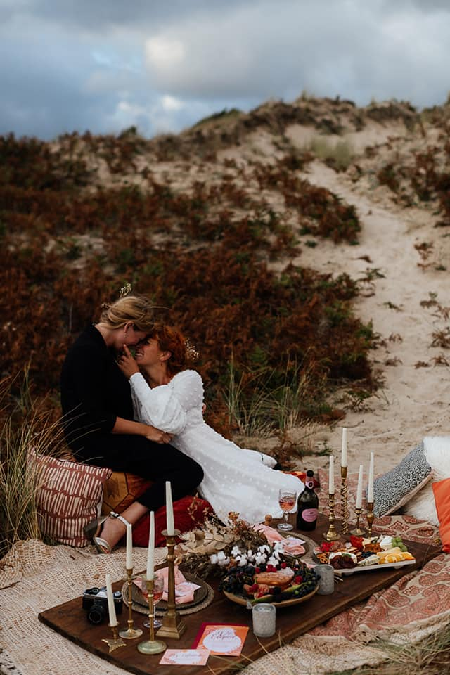 A wedding couple is kissing each other an sitting on a blanket on the beach near Jersey.