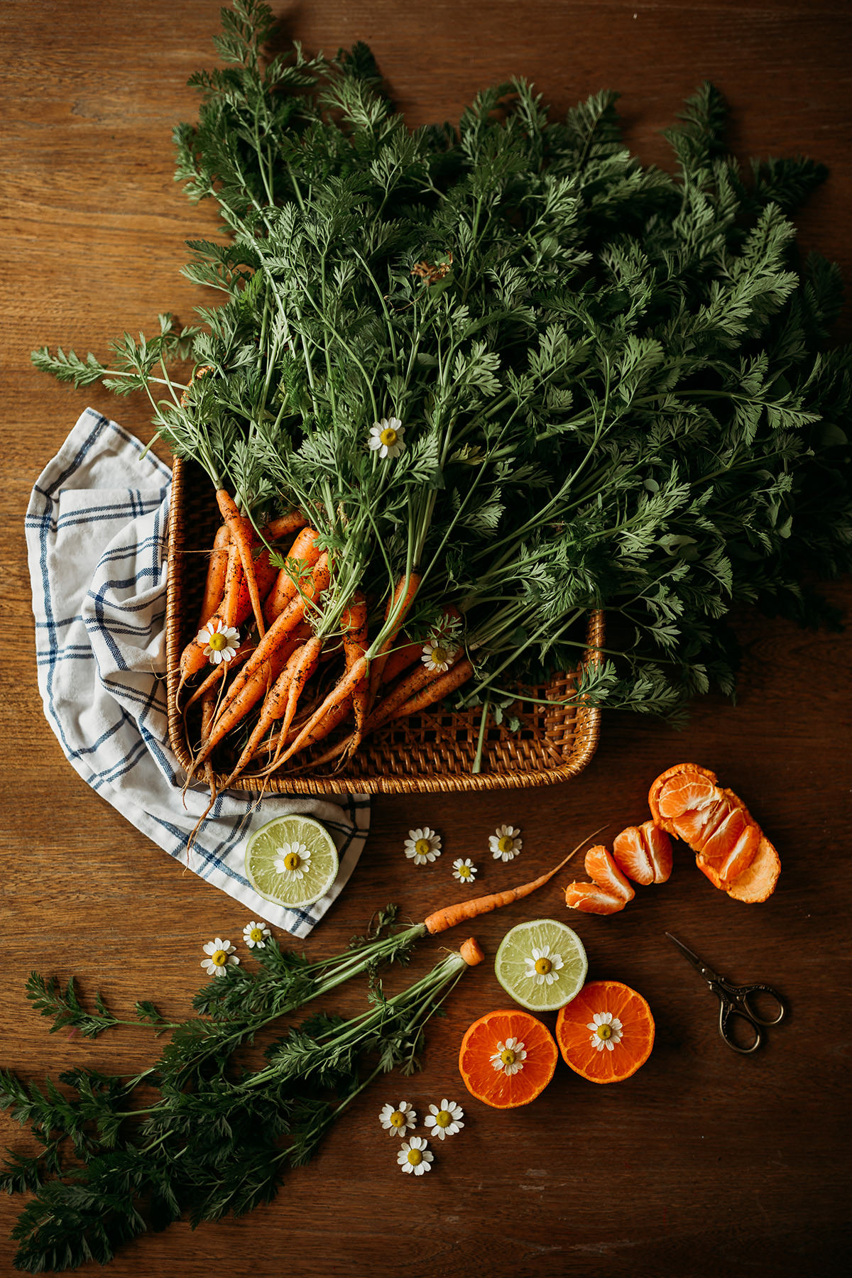 Fresh carrots, lemons, and tangerines perfectly arranged on a wooden surface