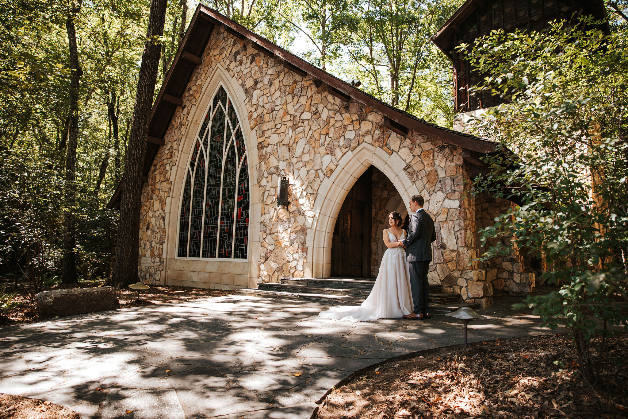 A wedding couple is standing in front of the Ida Cason Memorial Chapel at Callaway Gardens.