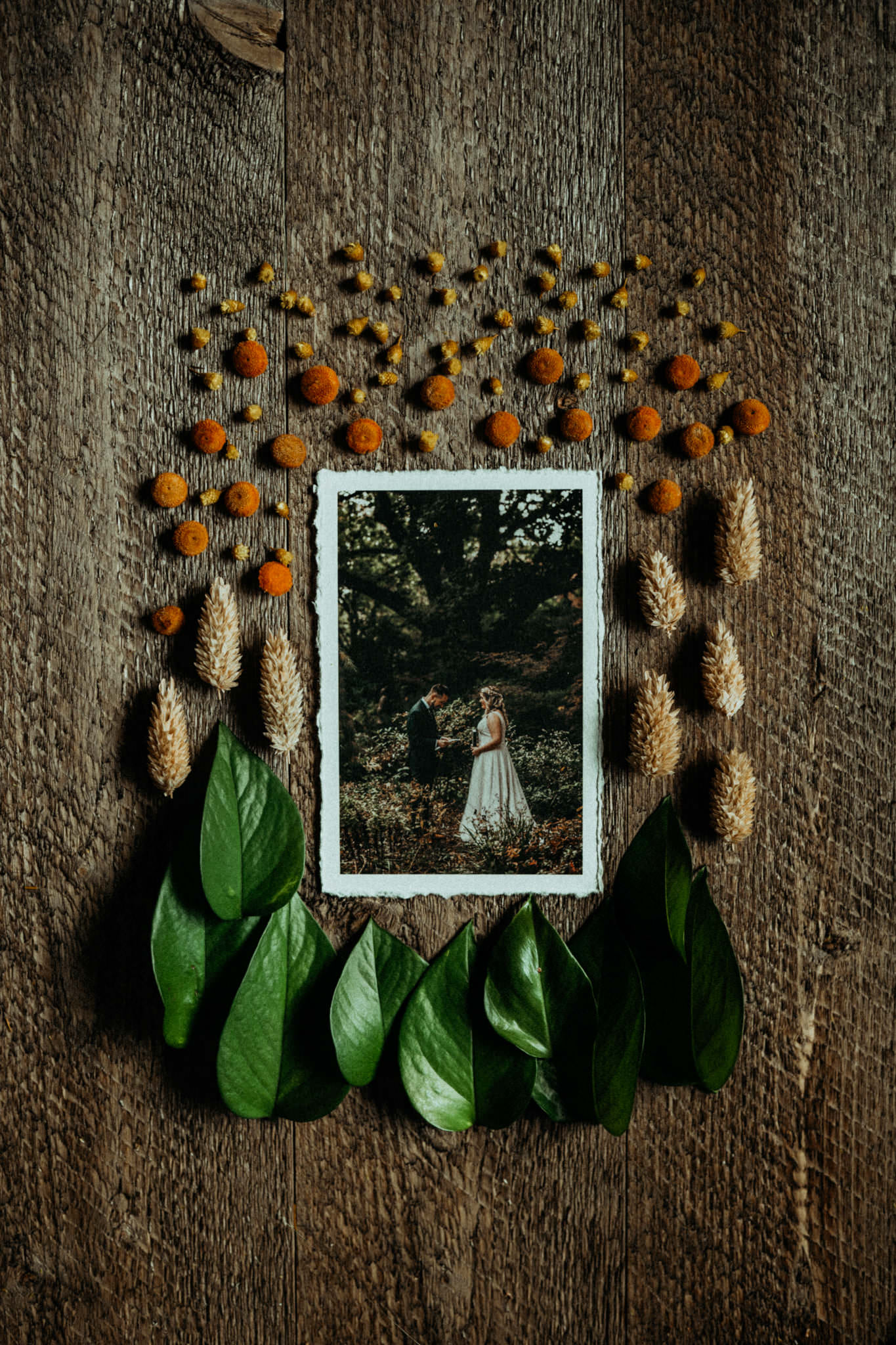 a wedding photo on a table surrounded by leaves and blossoms