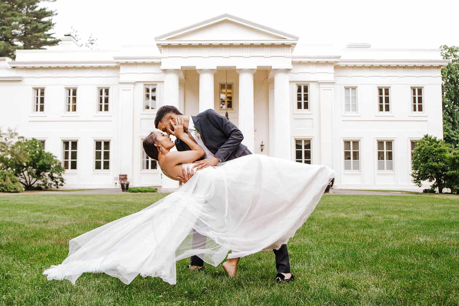 A wedding couple is kissing in front of a big building, captured by a wedding photographer Connecticut.