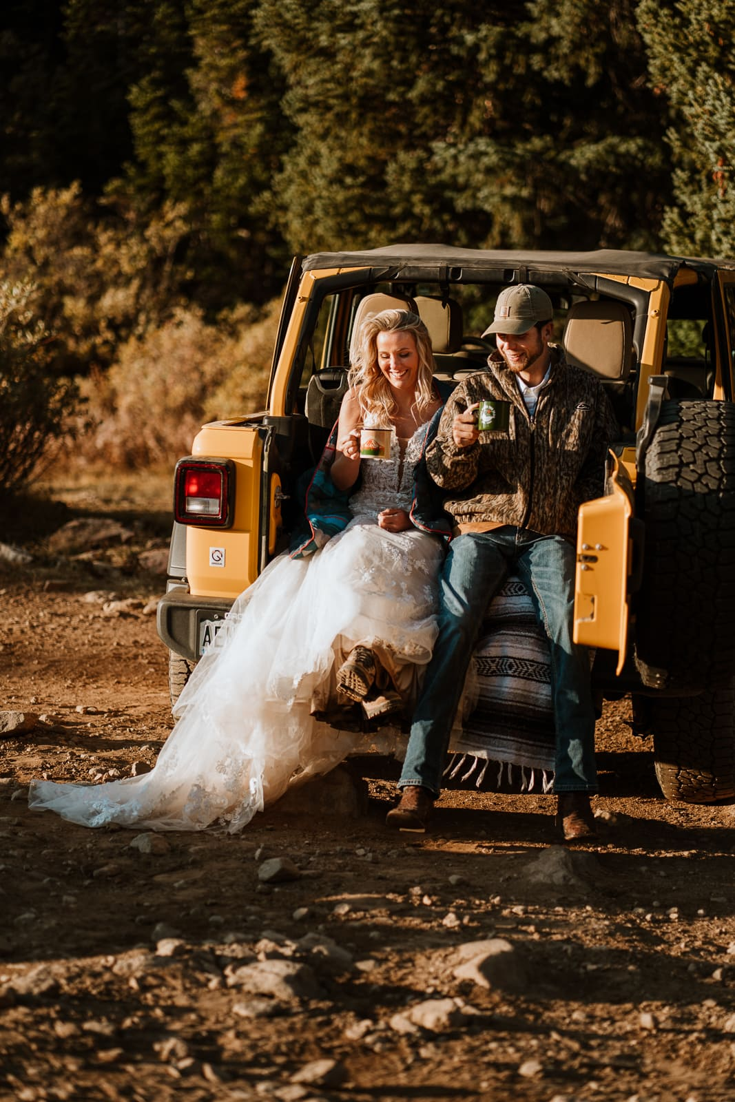 A wedding couple is sitting in the back of a Jeep and is driving hot beverages.