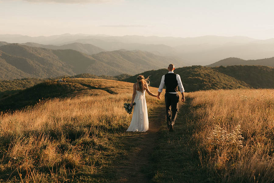 A wedding couple is walking on a path and is holding hands.