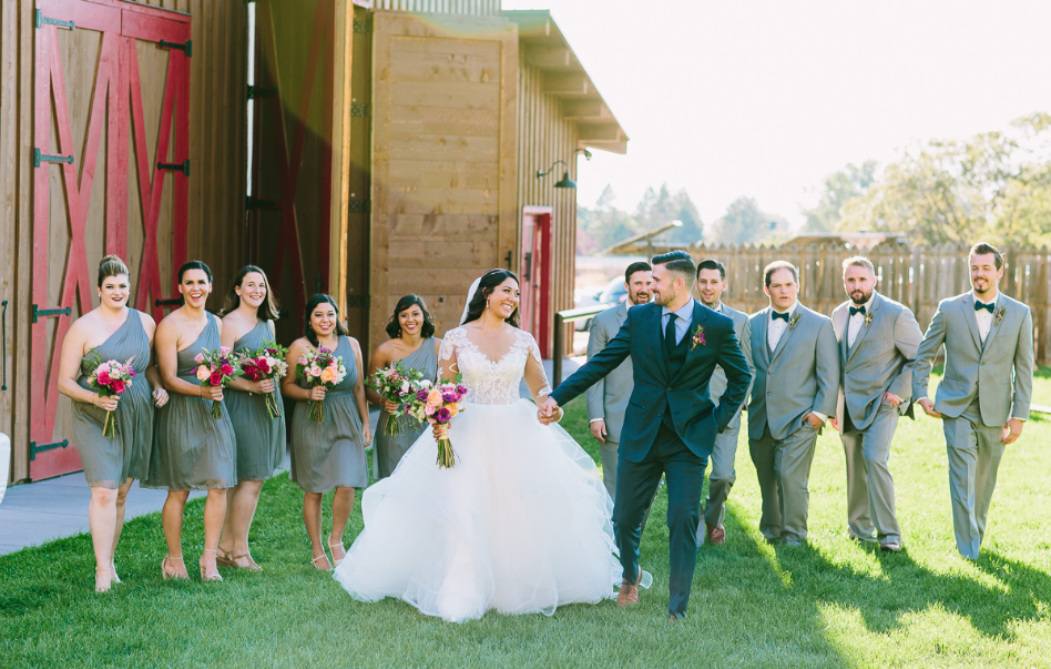A wedding couple and their bridesmaids and groomsmen are standing next to the quiet meadow farm in Utah.