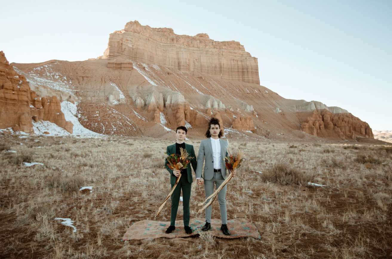 A wedding couple is standing in the middle of the Goblin Valley State Park and is holding hands.