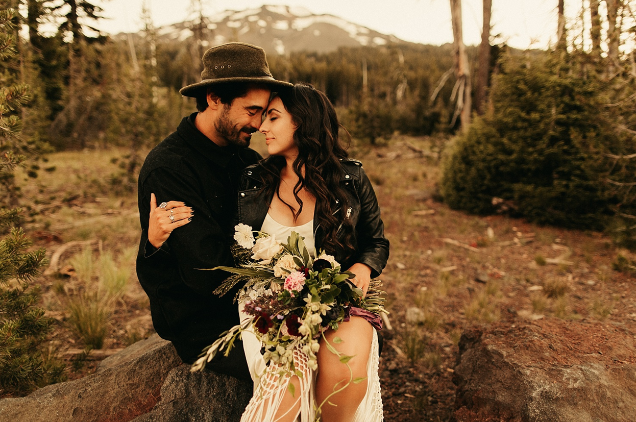 A wedding couple is holding each other and sitting on a rock near Mount Bachelor.