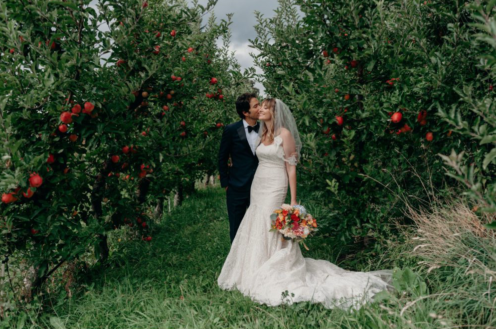 A wedding couple is kissing each other at Mt Hood Organic Farms.