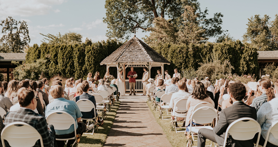 A wedding couple is getting married next to a pavilion and their guests are sitting next to the aisle, in the Village Green resort.